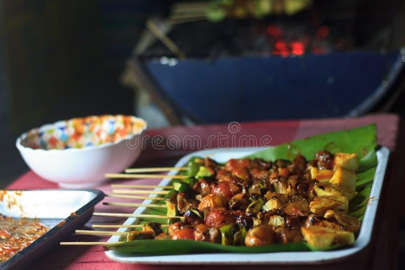 Traditioneel Aziatisch voedsel bij markt Heerlijk kruidig geroosterd kippenvlees op stokken royalty-vrije stock afbeelding