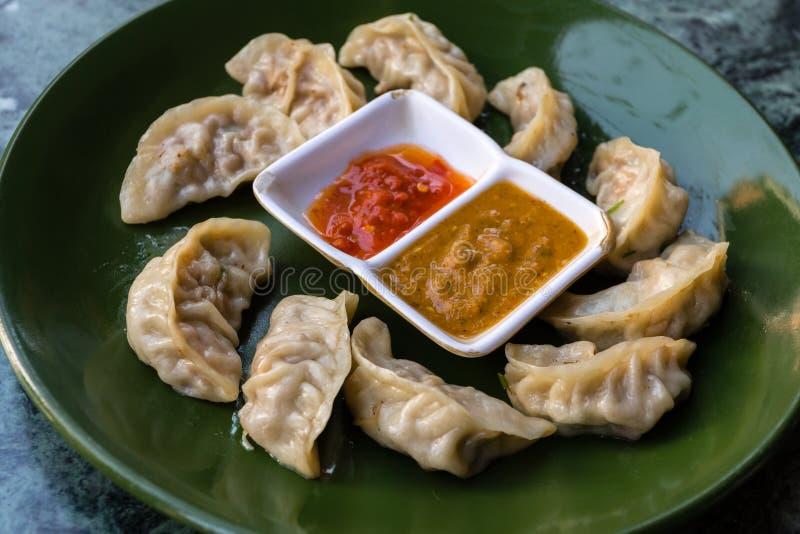 Traditioneel Aziatisch voedsel Nepalese gestoomde bolmomo die met tomatenchutney wordt gediend stock afbeeldingen