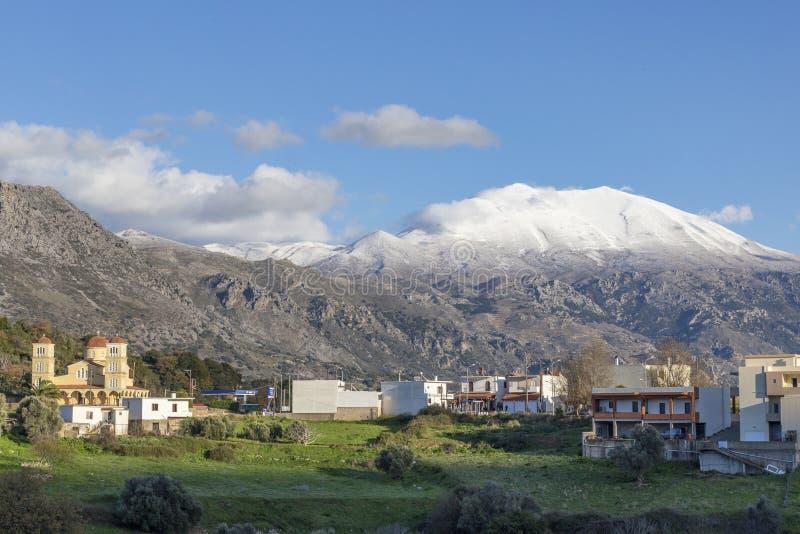 Traditioneel dorp in berg met sneeuwbergen en blauwe hemel op achtergrond kreta royalty-vrije stock fotografie
