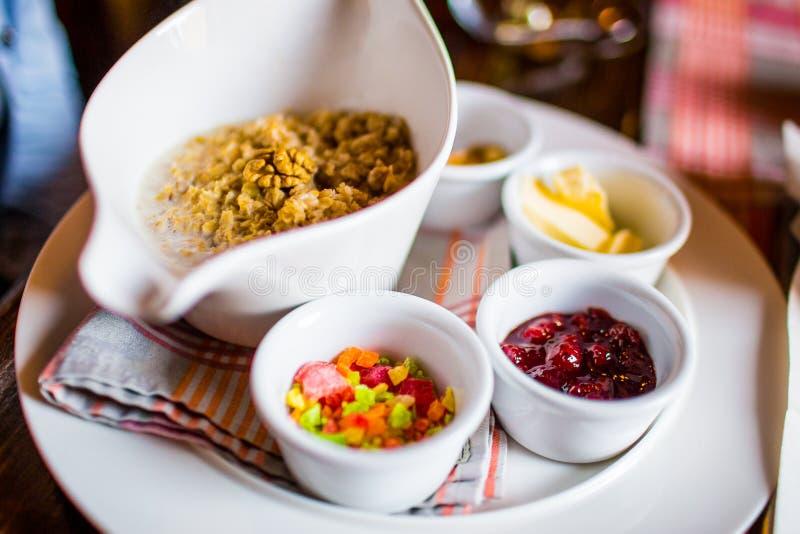 Traditioneel Engels ontbijthavermeel, jam, boter en gedroogd fruit op plaat royalty-vrije stock fotografie