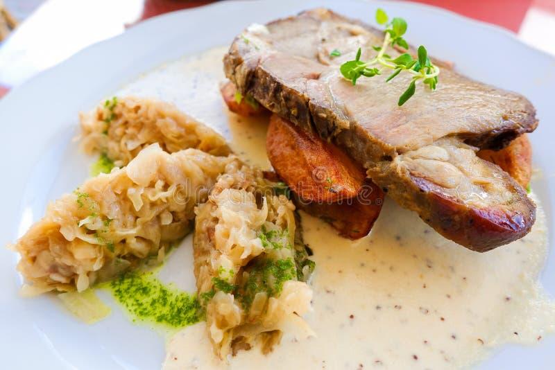 Traditioneel Estlands voedsel; zuurkoolhutspot met varkensvlees en lapje vlees, met gebraden aardappels wordt gediend die royalty-vrije stock afbeeldingen
