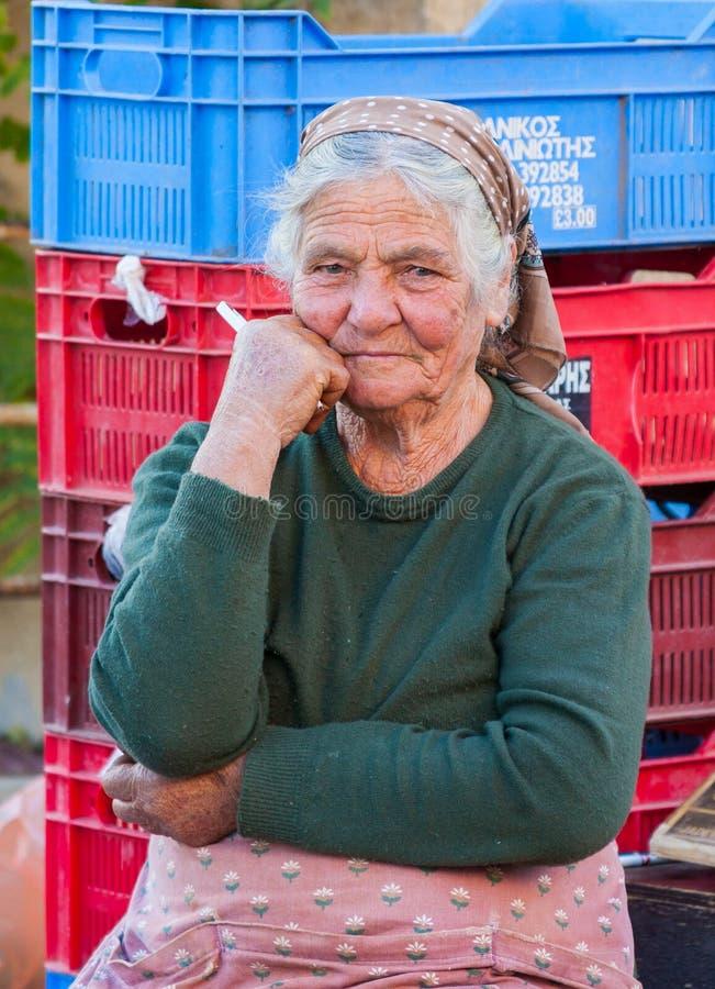 Traditioneel geklede oude vrouwenlandbouwer aan het werk die haar produ verkopen royalty-vrije stock afbeeldingen