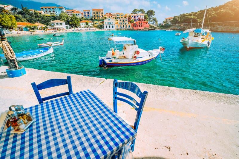 Traditioneel Grieks restaurant met blauwe en witte lijst en stoelen bij de overzeese kust van Assos-dorp Azuurblauw water royalty-vrije stock fotografie