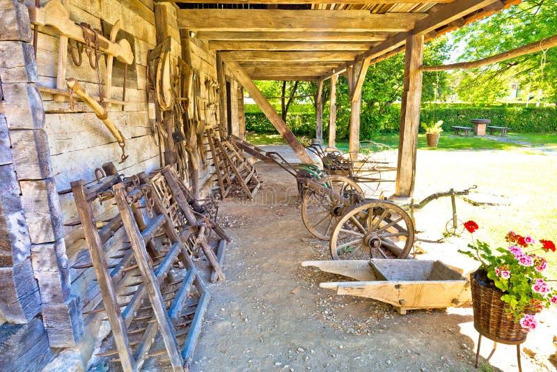 Traditioneel houten plattelandshuisje en landbouwhulpmiddelen in landelijke regio royalty-vrije stock foto's
