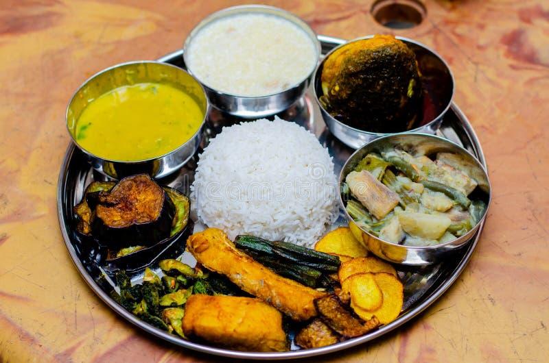 Traditioneel Indisch voedsel, Bengaalse voedselthali, rijst, dal, vissen, en groenten stock foto
