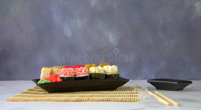 Traditioneel Japans die voedsel, een sushi met gember en wasabi op een bamboemat wordt geplaatst, eetstokjes en een kom met sojas royalty-vrije stock afbeelding