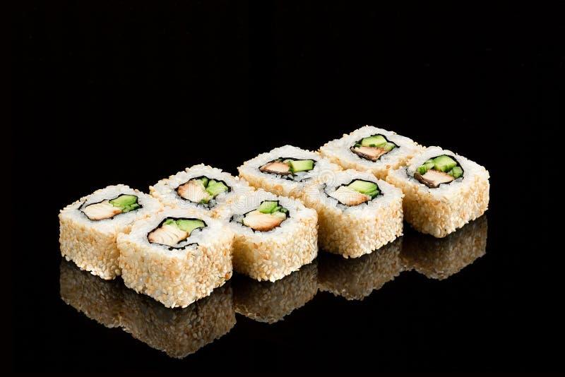 Traditioneel Japans sushibroodje met overzeese paling op een glanzende zwarte achtergrond stock foto's