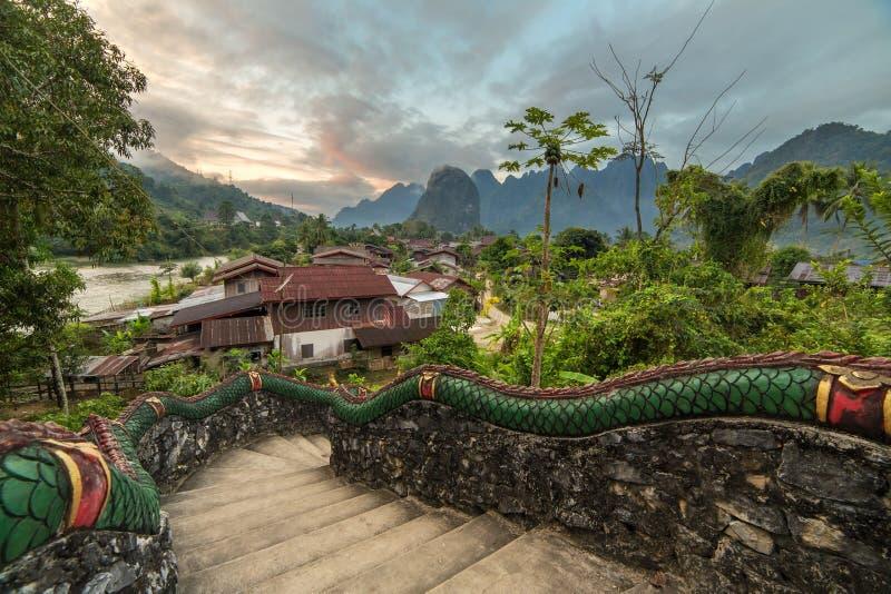 Traditioneel lao dorp met tempeltreden en bergachtergrond dichtbij Vang Vieng royalty-vrije stock afbeelding