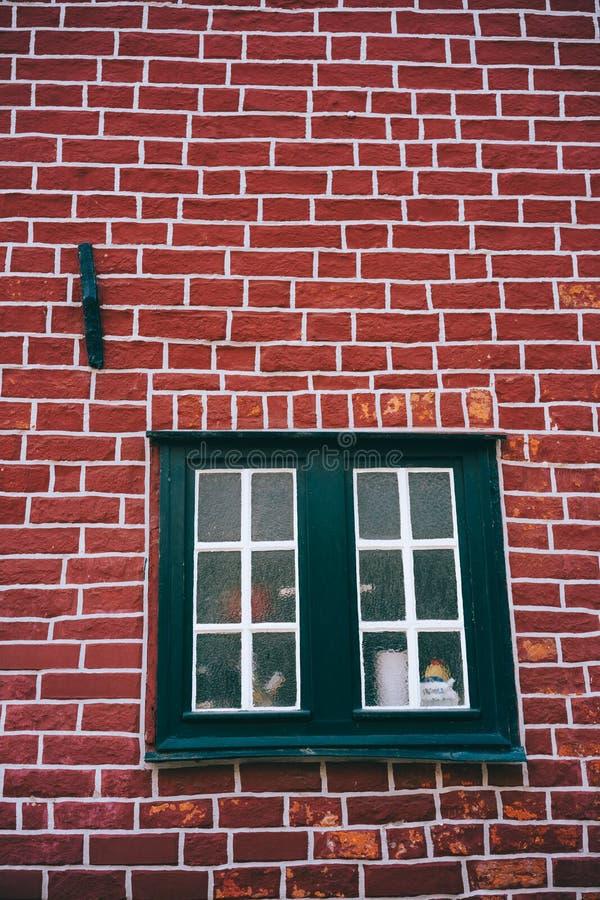 Traditioneel middeleeuws Duits baksteenhuis in Luneburg, Duitsland Fragment van de rode baksteenvoorgevel met raamkozijnen stock afbeelding