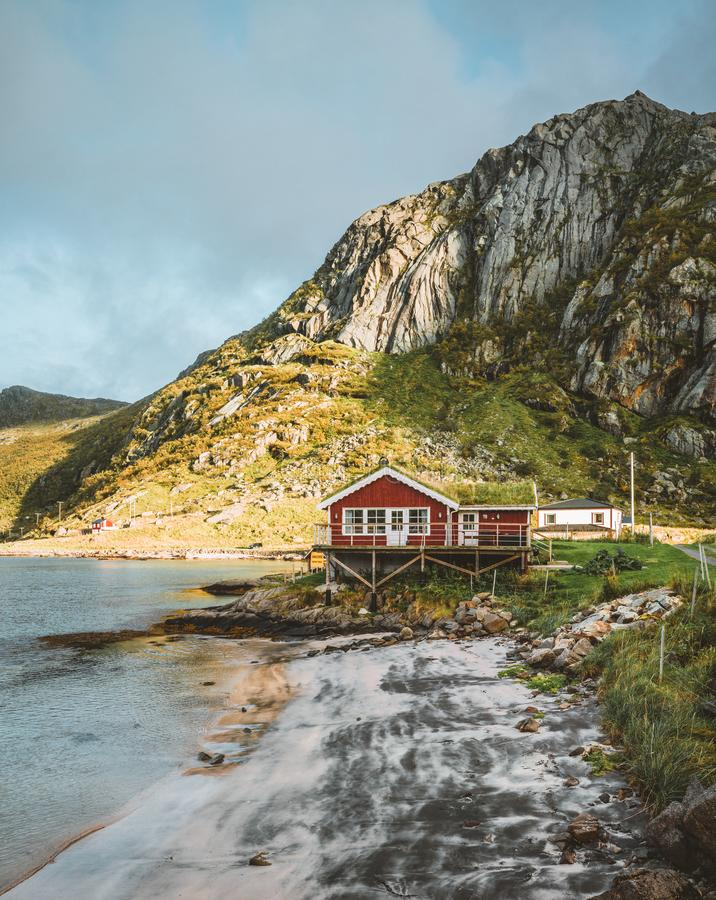 Traditioneel rood fishinhuis in Bjoernsand dichtbij Reine in Lofoten, Noorwegen met rode rorbuhuizen Zonsondergangmiddag met stock foto