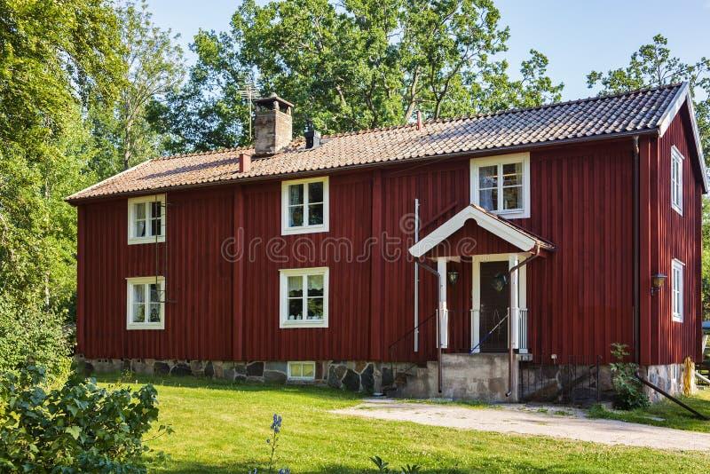 Traditioneel rood houtplattelandshuisje stock foto
