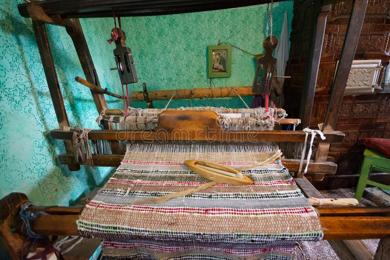 Traditioneel tapijt die machine in oud traditioneel huis van Roemenië maken stock foto