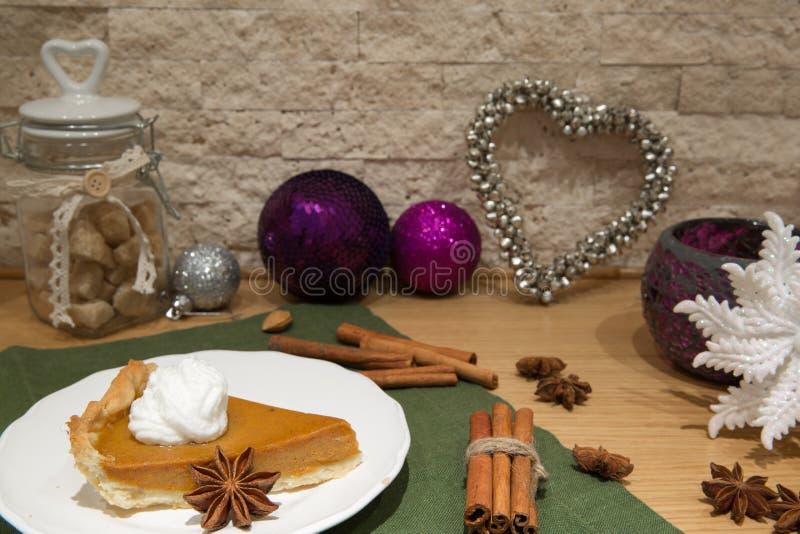 Traditionele Amerikaanse pompoenpastei met slagroom, bruine rietsuiker Hartdecoratie, violette Kerstmisballen en bruine suiker stock foto