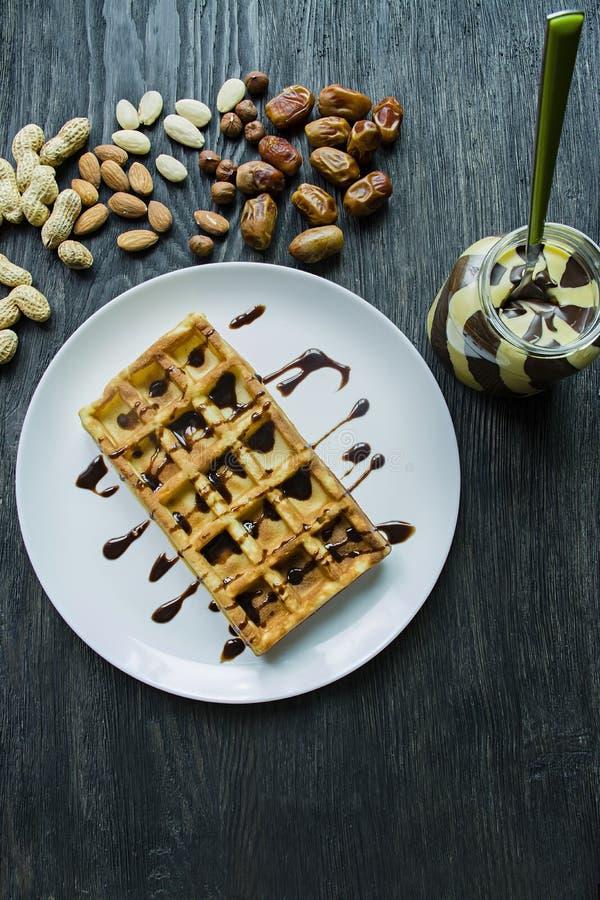 Traditionele Belgische die wafels in chocolade op een donkere houten achtergrond worden behandeld Smakelijk Ontbijt Verfraaid met stock foto's