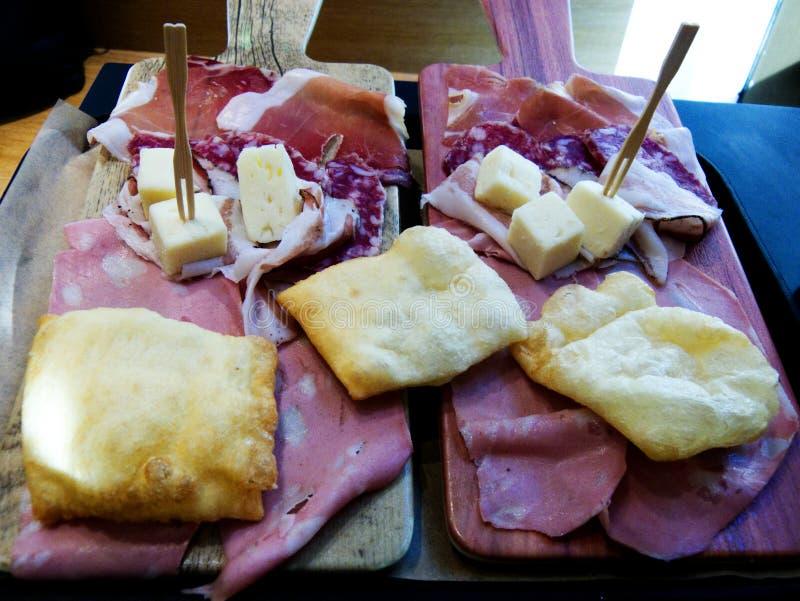 Traditionele bolognese maaltijd, mortadella, crescentine, salame, kaas Bologna, Italië stock foto's