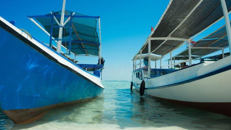 Traditionele boot dichte omhooggaand verankerd in strandkust met transparante duidelijke overzees royalty-vrije stock afbeeldingen