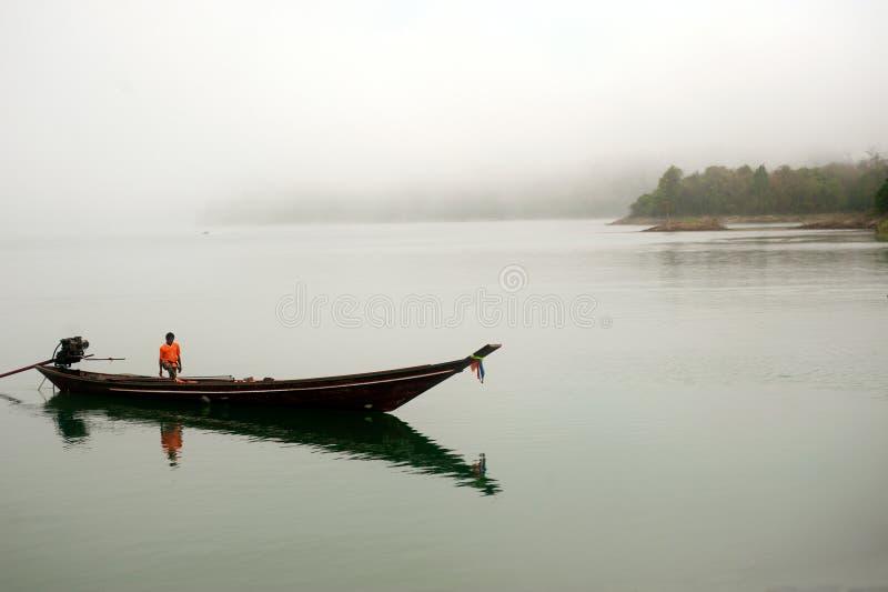 Traditionele boot wachtende toeristen in het meer van Cheow Larn, Thailand stock foto's