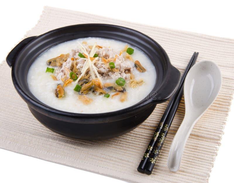 Traditionele Chinese die de rijsthaverbrij van de varkensvleeshavermoutpap in claypot wordt gediend stock fotografie