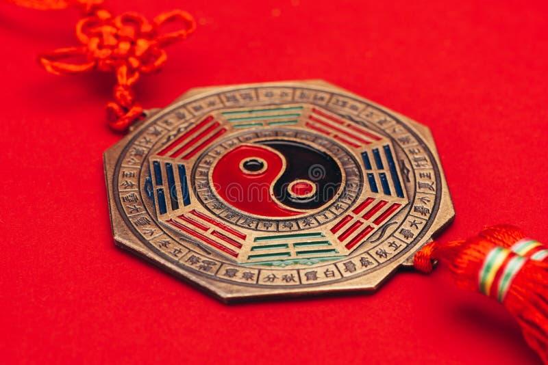 Traditionele Chinese yin en yang amulet op rode oppervlakte stock afbeeldingen