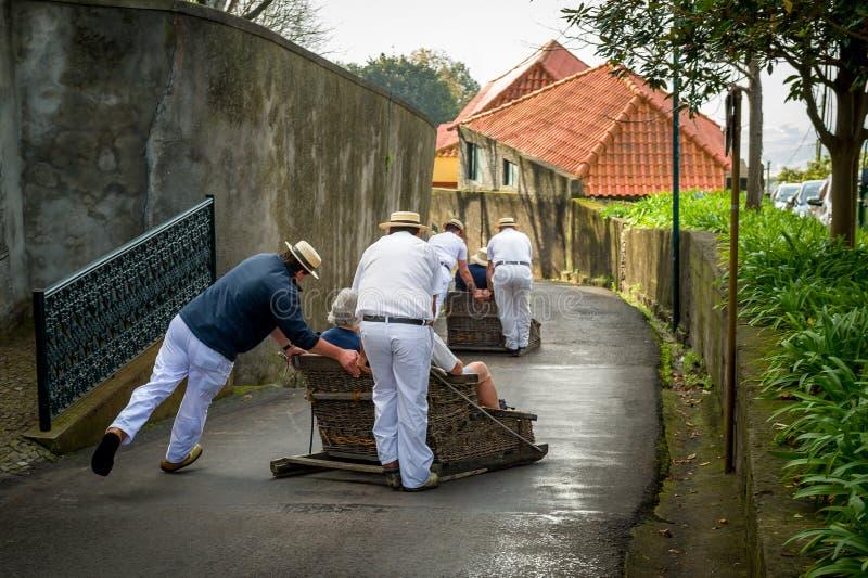Traditionele de slee bergaf ruiters van Funchal in Monte-park stock foto's