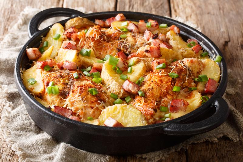 Traditionele die kippenborst met aardappels, bacon en kaas wordt gebakken stock afbeeldingen