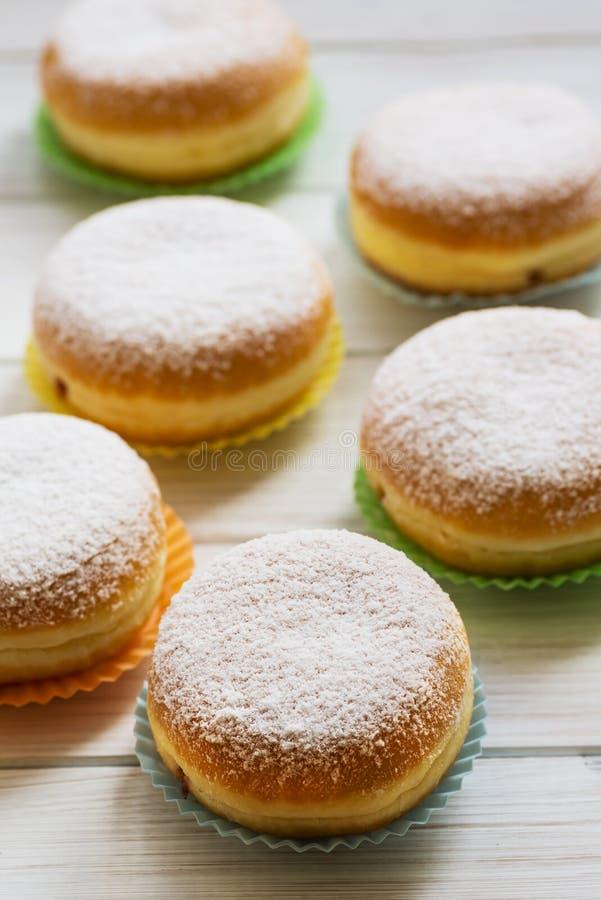 Traditionele Duitse Poolse die Doughnut met Frambozenjam met Suikerglazuursuiker wordt bestrooid stock fotografie