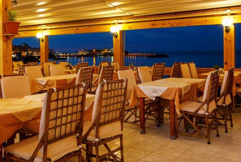 Traditionele Europese koffie in nacht op eiland van de nacht van Kreta Griekenland Houten stoelen met witte tafelkleden op de Baa stock foto