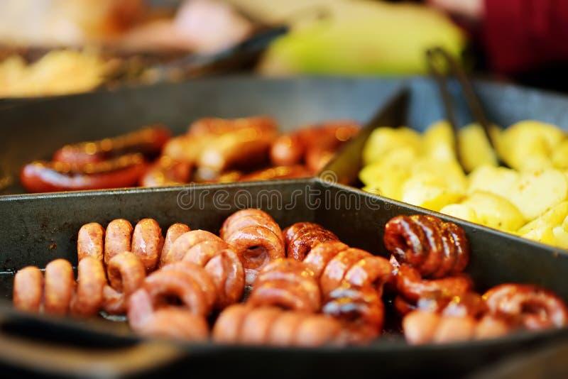 Traditionele gefrituurde worst die wordt gekookt op de voorjaarsmarkt in Vilnius, Litouwen Ras straatvoedsel op paasbeurs stock foto's