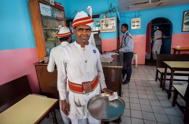 Traditionele geklede bejaarde kelner die van populair Indisch restaurant op klanten wachten stock afbeelding