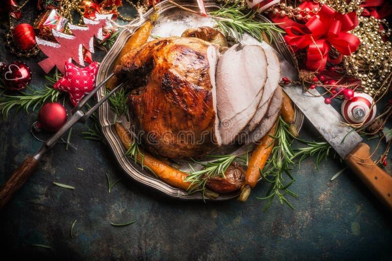 Traditionele gesneden geroosterde verglaasde Kerstmisham met vakantie feestelijke decoratie op donkere rustieke achtergrond, hoog royalty-vrije stock fotografie
