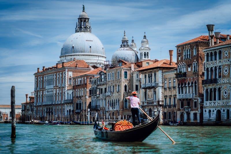 Traditionele Gondel en gondelier op Kanaal Grande met Basiliekdi Santa Maria della Salute op de achtergrond in Venetië stock afbeelding