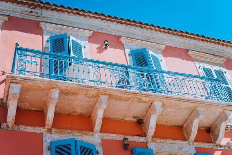 Traditionele Griekse huisvoorgevel met blauwe vensters, blinden en balkons, Griekenland stock foto