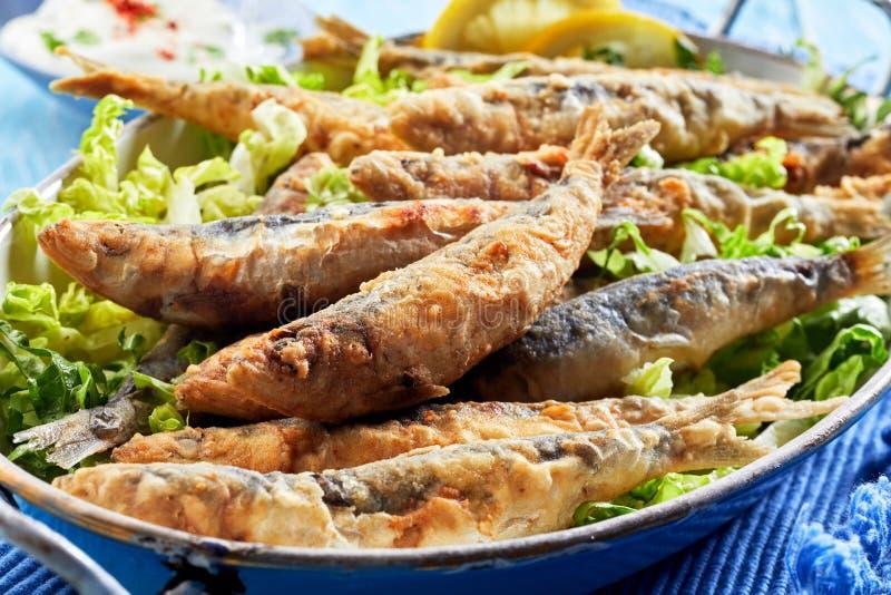 Traditionele Griekse knapperige gebraden sardines in beslag stock foto's