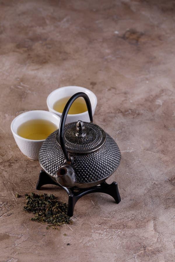Traditionele groene die thee in een gietijzertheepot wordt gekookt met droge kruiden en twee het drinken kommen op een geweven ac royalty-vrije stock foto