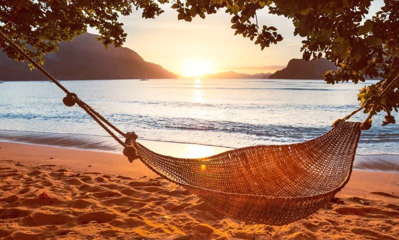 Traditionele hangmat in de schaduw bij zonsondergang op een kalm tropisch strand royalty-vrije stock foto's