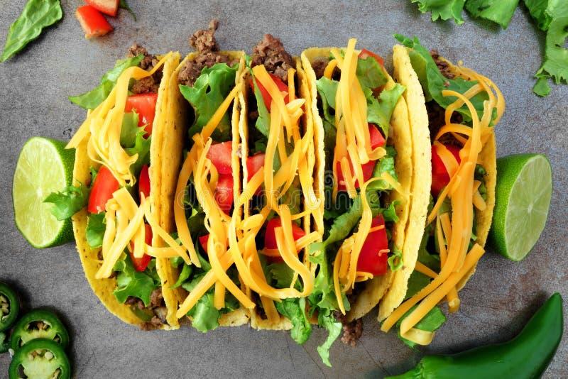 Traditionele harde geschilde taco's, luchtmening op rustiek dienblad stock fotografie
