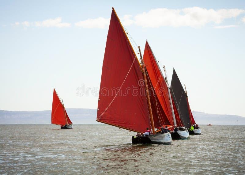 Traditionele houten boten met rood zeil stock fotografie