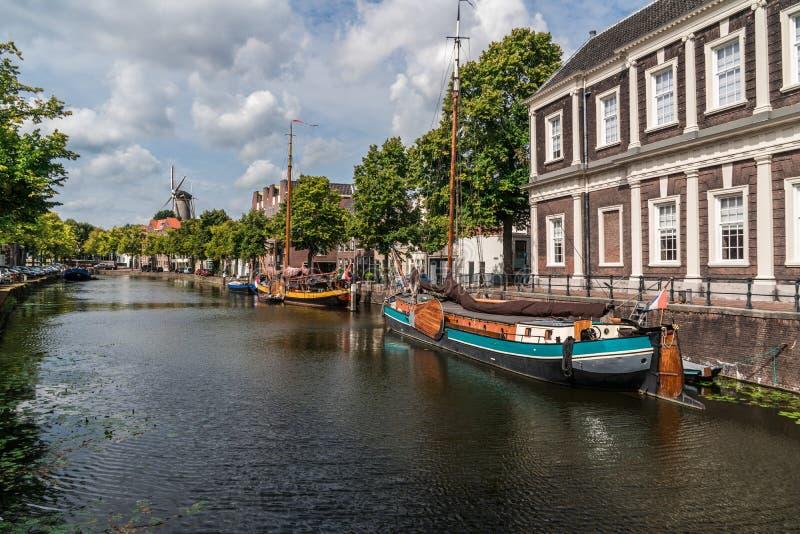 Traditionele houten varende schepen in waterkanaal Windmolen achter gebouwen Oude historische haven van Schiedam, stock fotografie