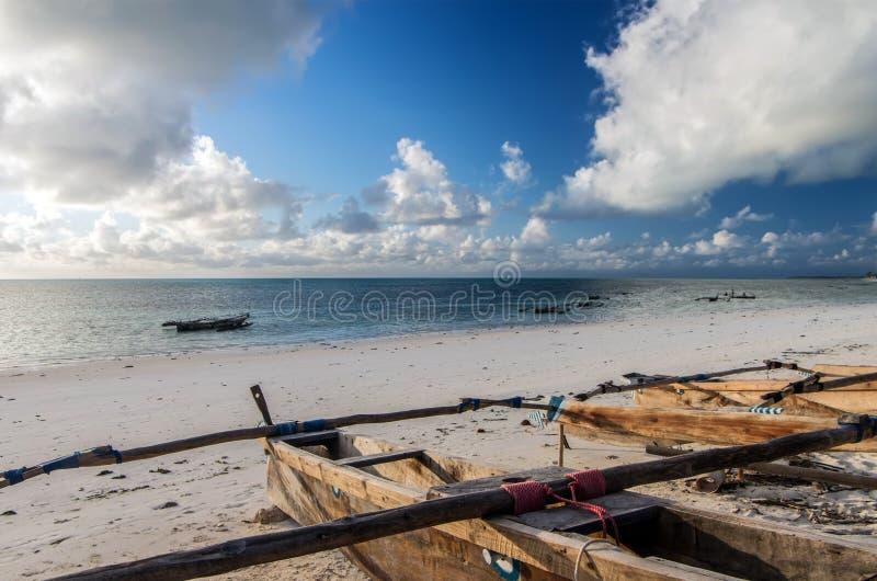 Traditionele houten vissersboten in het Oosten van Zanzibar Wolken over de Indische Oceaan Schitterende zonsopgang over de oceaan stock afbeelding