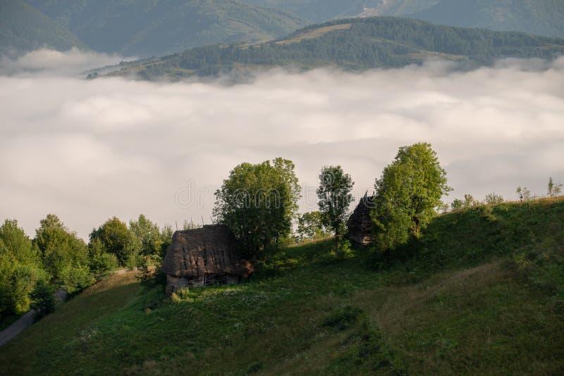 Traditionele huizen in Transsylvanië, zonsopgang met mist in de bergen, Roemenië royalty-vrije stock afbeeldingen