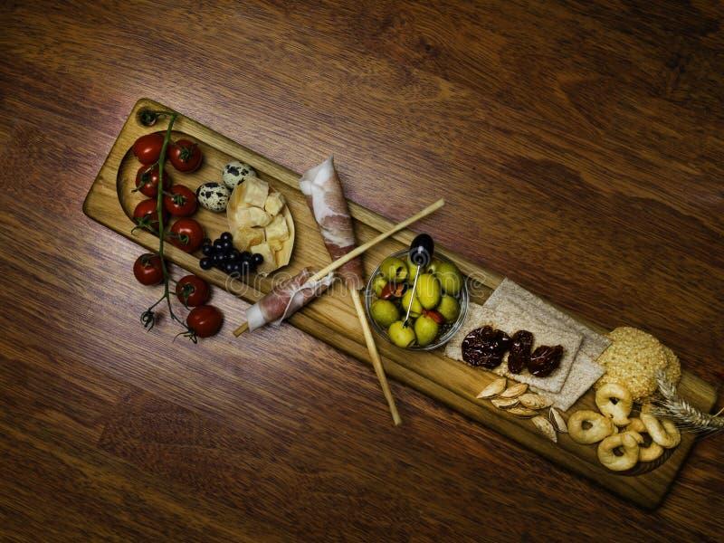 Traditionele Italiaanse antipasto met prosciutto, parmezaanse kaaskaas, in de zon gedroogde tomaten, groene olijven, kwartelseier stock foto