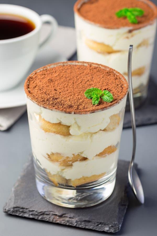 Traditionele Italiaanse die Tiramisu-dessertcake in een glas, met cacaopoeder en munt, met kop van koffie, op grijs wordt verfraa royalty-vrije stock afbeelding