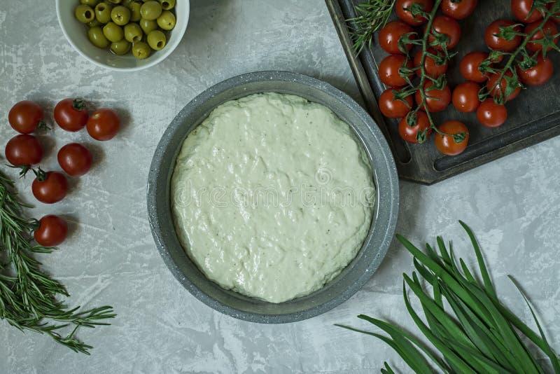 Traditionele Italiaanse Focaccia met tomaten, olijven en rozemarijn Focaccia het koken proc?d?, ingredi?nten Focacciadeeg stock foto