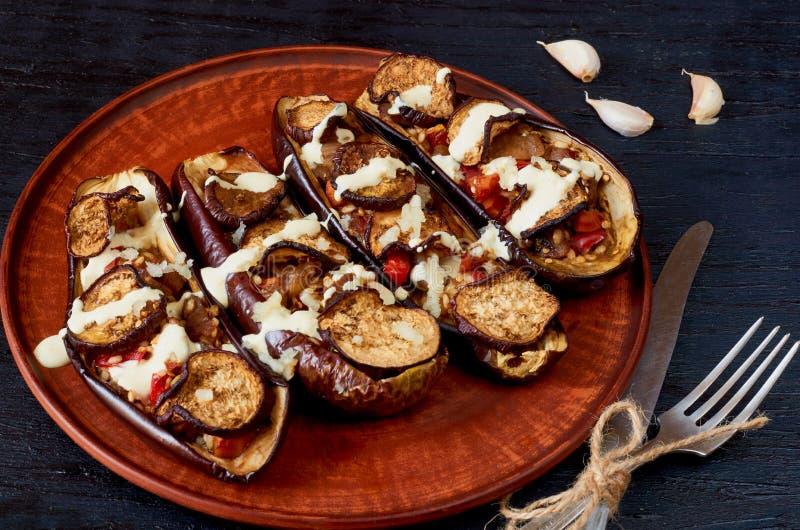 Traditionele Italiaanse schotel - de geroosterde aubergines vulden met stijging, tomaten, knoflook en saus op een uitstekende pla royalty-vrije stock foto's