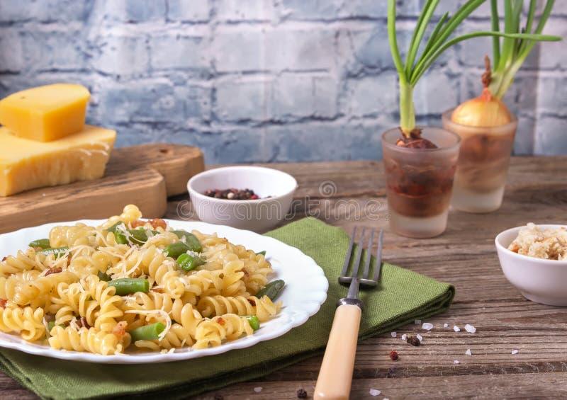 Traditionele Italiaanse Siciliaanse die fusillideegwaren met broodcrumbs en slabonen, met kaas in een witte plaat op houten wordt royalty-vrije stock fotografie