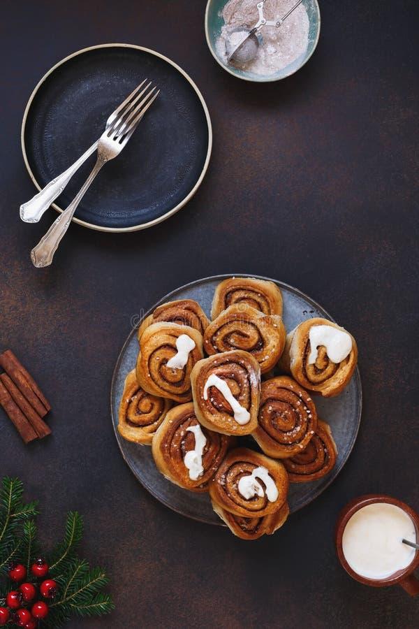 Traditionele kaneelbroodjes met verglazing op feestelijke lijst stock fotografie