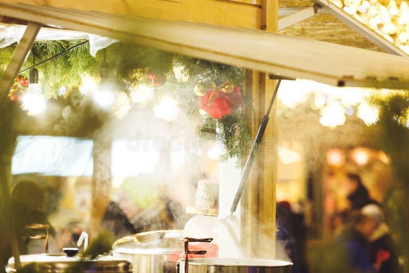 Traditionele Kerstmisbox bij nieuwe jaar en Kerstmismarkt met lichten, decoratie, vaten met hete theeën, overwogen wijn stock afbeeldingen