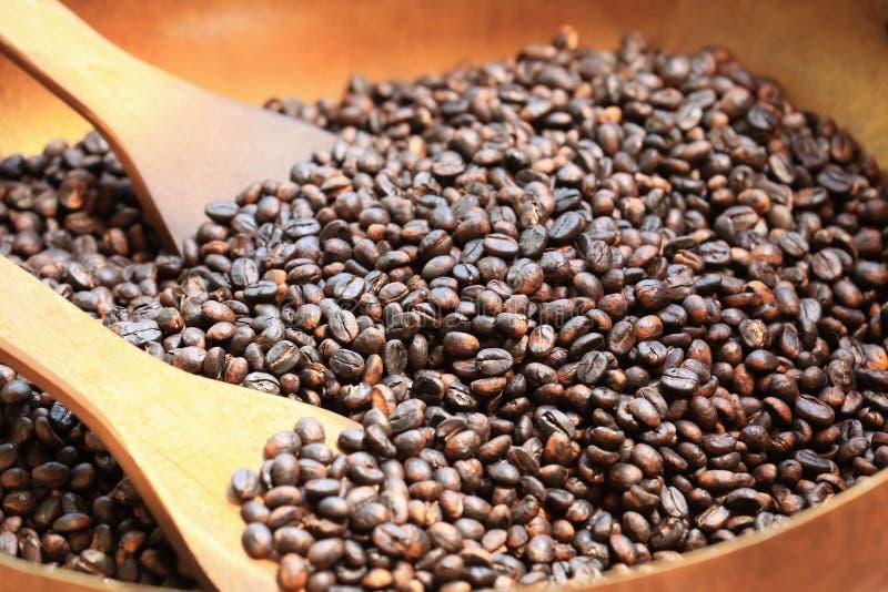 Traditionele koffiebonen die in metaalbassin roosteren met spatel royalty-vrije stock foto