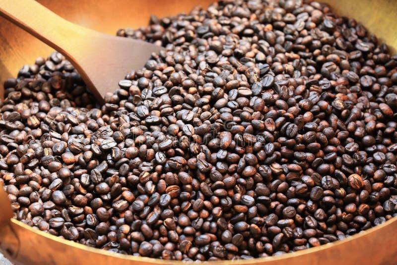 Traditionele koffiebonen die in metaalbassin roosteren met spatel stock fotografie