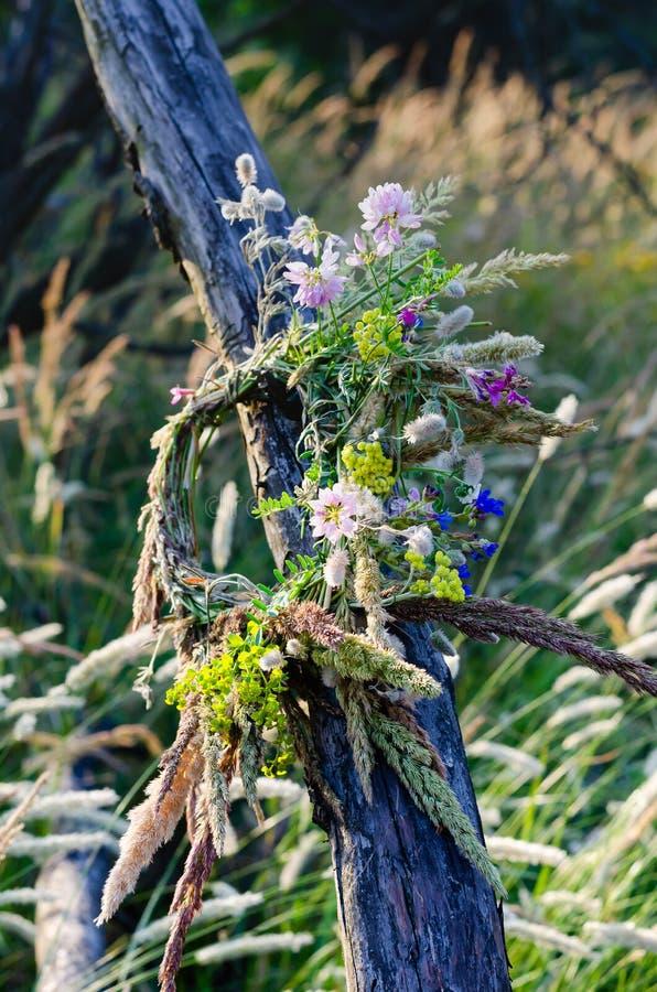 Traditionele kroon van gebiedskruiden en bloemen op een oude droge boomboomstam Inzameling en Voorbereiding voor de rite van vier stock foto